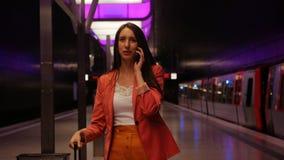 等待的地铁-一个年轻女商人谈话在智能手机和笑 影视素材
