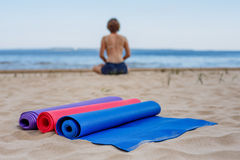 等待的学生-瑜伽席子在沙子说谎 图库摄影