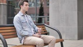 等待的年轻人坐长凳和检查时间