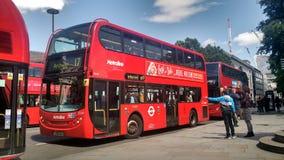 等待红色公共汽车的人 免版税库存图片
