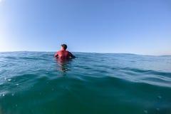 等待蓝色海洋天际的冲浪者 免版税库存图片