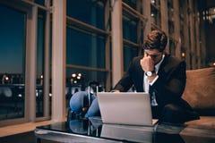 等待被延迟的飞行的疲乏的商人在机场休息室 免版税库存照片