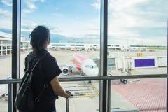 等待飞行的妇女在机场;窗口机场 年轻女人在机场,注视着通过窗口飞机 免版税库存照片