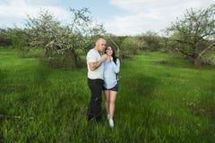 等待婴孩的夫妇吹在蒲公英 图库摄影