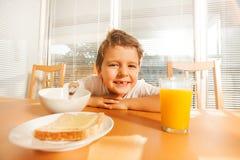 等待他的早餐的愉快的男孩在厨房里 免版税库存照片