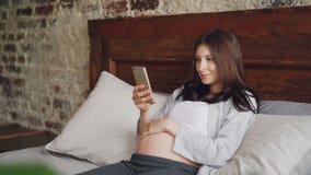 等母亲的可爱的少妇在床使用智能手机,抚摸她腹部和微笑的在家说谎 现代 股票录像