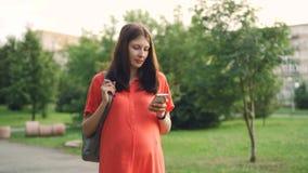 等母亲的美丽的怀孕的女孩在城市公园走,并且使用智能手机,少妇是保存设备和 影视素材