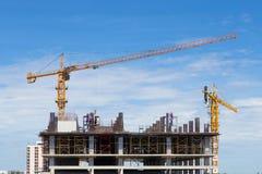 建筑业的建筑用起重机和工作者与蓝天的 免版税图库摄影