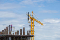 建筑业的建筑用起重机和工作者与蓝天的 免版税库存照片