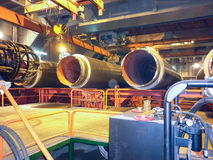 建筑传递途径拖拉机二 管子的零件在铺管船的举行 免版税库存照片