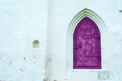 建筑学元素建筑学视图变老了黑暗的洋红色金属与拱廊的伪造的门在白色石墙上 库存照片