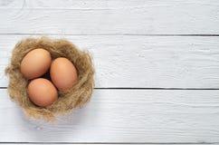 筑巢用在白色木板条背景的鸡蛋 免版税图库摄影