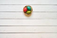筑巢色的鸡蛋缠绕在白色木板条背景 免版税库存照片