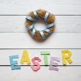 筑巢花圈,复活节折叠了纸在白色木板条土气背景的origami五颜六色的字法 免版税库存照片