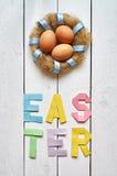 筑巢花圈,鸡蛋,复活节折叠了纸在白色木板条土气背景的origami五颜六色的字法 图库摄影