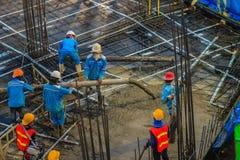 建筑工人倾吐在之后紧张floori的混凝土 免版税库存图片