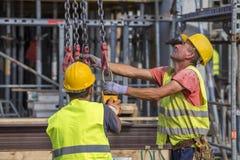 建筑工人准备对举混凝土桩模子 免版税图库摄影