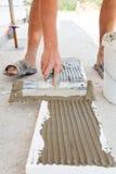 建筑工人在与小铲的聚苯乙烯泡沫塑料上把石膏放 库存照片