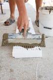 建筑工人在与小铲的聚苯乙烯泡沫塑料上把石膏放 免版税库存图片