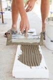 建筑工人在与小铲的聚苯乙烯泡沫塑料上把石膏放 免版税图库摄影