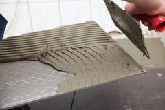 建筑工人在家铺磁砖砖地胶粘剂 免版税库存图片