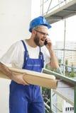 建筑工人工作成套装备的和盔甲的站立在一个建造场所的一个高处有计划的在他的胳膊下 免版税库存照片
