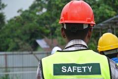 建筑工人穿戴安全背心有对此的安全标志 免版税库存照片