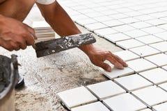 建筑工人被胶合的陶瓷砖地板 免版税库存照片