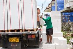 建筑工人移动砖。 免版税库存图片