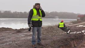建筑工程师谈话在手机和工作者在排序铺的砖后 影视素材