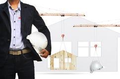 建筑师和举的建筑用起重机在家和安全帽 库存图片