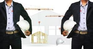 建筑师和举的建筑用起重机在家和安全帽 免版税库存照片