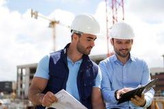 建筑师和工作者关于建造场所的制定计划会议 免版税库存照片