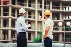 建筑师和建造者谈论在建造场所 免版税库存图片