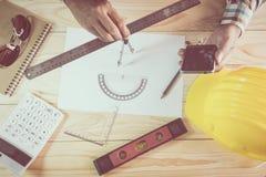 建筑师图画建筑的手在木书桌计划 免版税库存照片