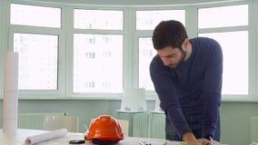 建筑师在书桌上把安全帽放