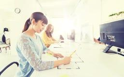 建筑师在图纸的妇女图画在办公室 免版税库存图片