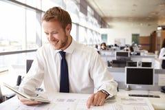 年轻建筑师在工作在使用片剂计算机的一个办公室 免版税库存照片