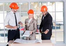 建筑师在工作 在办公室遇见的三位建筑师 库存照片