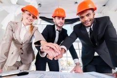 建筑师在手上的被放置的手 三businessmеn建筑师遇见 库存照片