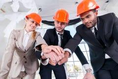 建筑师在手上的被放置的手 三businessmеn建筑师遇见 免版税图库摄影