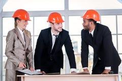 建筑师在手上的被放置的手 三businessmеn建筑师遇见 免版税库存照片