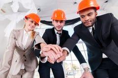建筑师在手上的被放置的手 三businessmеn建筑师遇见 库存图片