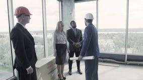 年轻建筑师审阅被修理的大厦前提,谈话在智能手机 股票视频