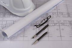 建筑师工作场所-与测量的磁带、安全帽、玻璃和自动铅笔的建筑图纸在桌上 名列前茅vi 免版税库存照片