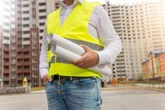 建筑师特写镜头摆在与图纸的安全背心的在ne 库存图片