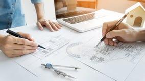建筑师设计谈论在桌上与图纸-克洛 免版税库存图片