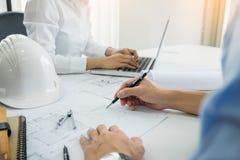 建筑师设计谈论在桌上与图纸-克洛 免版税图库摄影