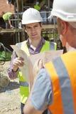 建筑师谈论计划与在建造场所的建造者 库存图片