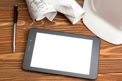 建筑师-建筑项目、计划、图纸卷和片剂个人计算机,笔,在空白纸的安全帽工作场所  免版税图库摄影
